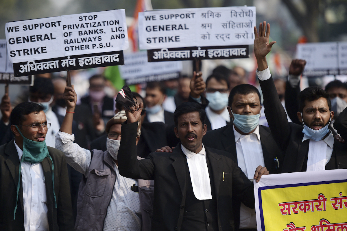 Men protesting with banners saying we support general strike