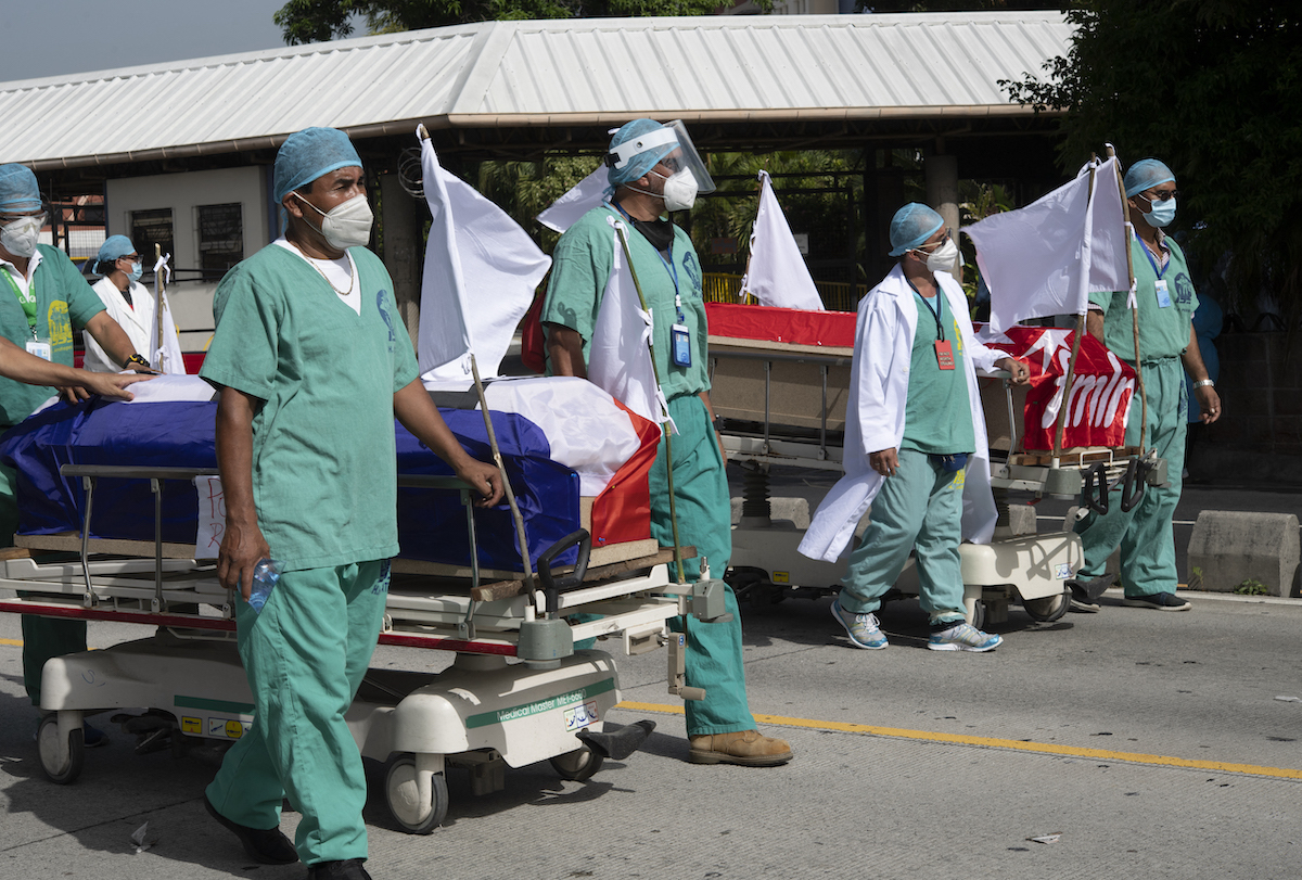 Doctors walking with coffin on a trolly
