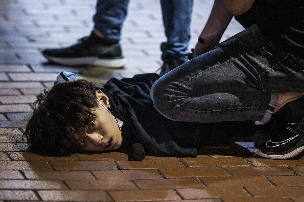 boy lying face down on the floor with someone kneeling over them holding them down